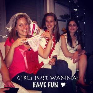 הכלה פותחת את המתנות במסיבת הרווקות שלה מחזיקה תחתונים ומחייכת שלידה החברות שלה צוחקות
